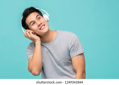 Happy young Asian man enjoying listening to music with headphones studio shot isolated on light blue background