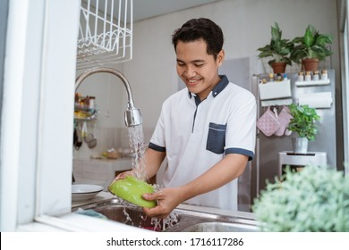 Happy young asian man in white shirt standing and washing dishes on the kitchen