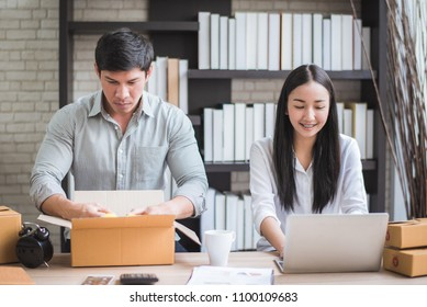 Happy young Asian man and woman at office of their business online shopping.