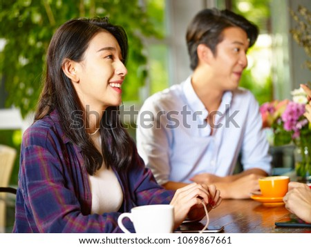 happy young asian man and woman in conversation with friends in coffee shop