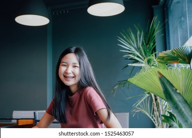Happy young asian millennial woman smiling with braces in green natural cafe, positive female teenager