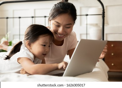 Happy young Asian mom and little ethnic daughter lying in bed at home watch video on modern laptop, smiling Vietnamese mother or nanny relax in bedroom with small biracial girl child using computer