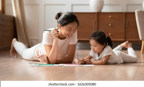 Happy young Asian mother and cute little biracial daughter lying on warm wooden floor in living room painting together, millennial ethnic mom or nanny relax with small Vietnamese girl child drawing