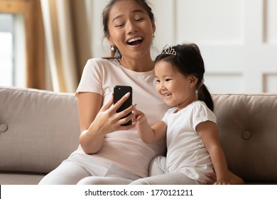 Happy young asian mother showing funny educational application on mobile phone to interested cute small kid daughter, relaxing together on sofa, excited family using digital gadget, watching videos.