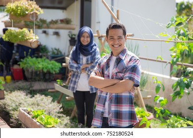 happy young asian people in rooftop garden. small urban farming concept