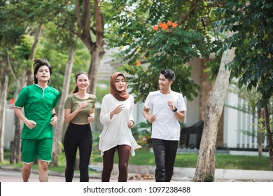happy young asian people working on exercise and warm up to jogging and running outdoors