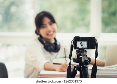 Happy young Asian singer woman beauty blogger or vlogger recording video viral clip at home for singing live and sharing online mass media by mirrorless camera on tripod