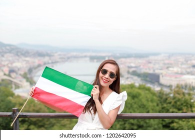 Happy young asian tourist woman with Hungarian flag standing on top view cityscape of Budapest city, Hungary