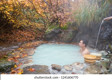 Happy Young Asian traveler Enjoy Soaking and Relaxing in Private Outdoor Milky White Hot Spring Onsen beside Stream River Flow and Beautiful Vibrant Autumn Tree in Nyuto Onsen Tohoku Japan