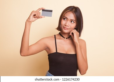 Happy young Asian woman with a blank card on beige background