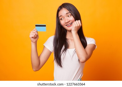 Happy young Asian woman with a blank card on bright yellow background