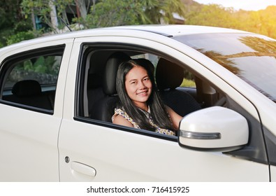 Happy young asian woman in a car while driving.