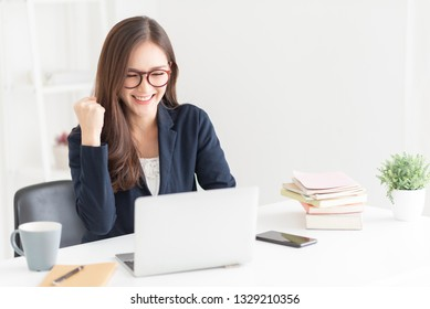 Happy young Asian woman is celebrating with raised hand up and at the office. Successful with Winning or victory gesture.