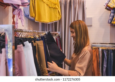 Happy young asian woman choosing clothes at store shop in shopping mall or department store