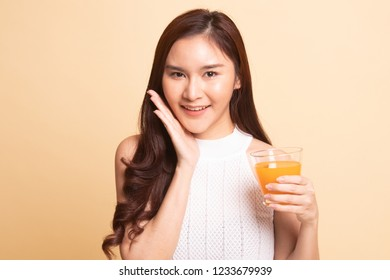 Happy Young Asian woman drink orange juice   on beige background