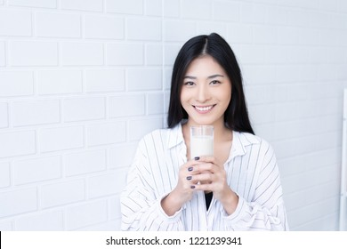 Happy young Asian woman drinking milk from the glass after exercise.over white background, shake looking at camera in the living room at home