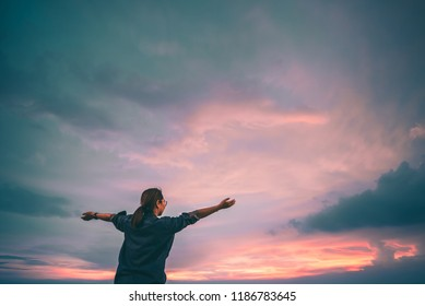 Happy young  asian woman enjoying freedom with open hands on the beach and sunset sky background.