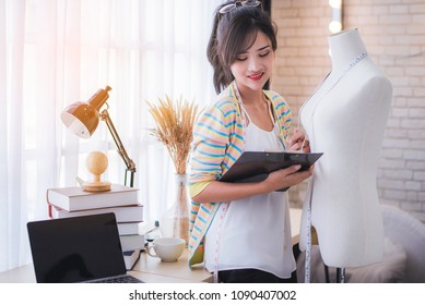 Happy young Asian woman fashion designer working in the studio