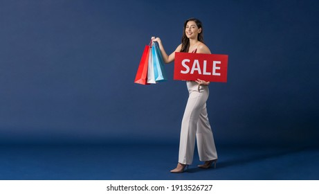 Happy young Asian woman holding and presenting sales paper banner for shopping on blue color background, cashless payment, black friday and consumerism concept, carrying shopping bags