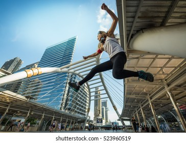 Happy young  Asian woman jumping high into the sky in the city background, business competition concept.