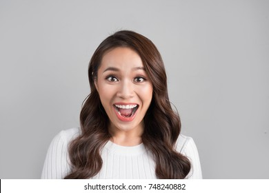 Happy young asian woman keeping mouth open looking at camera