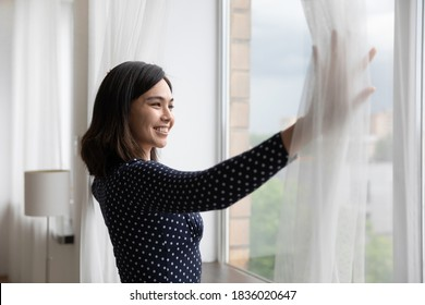 Happy young asian woman open curtains look in window distance dreaming or planning future success. Smiling Vietnamese female renter tenant meet welcome new sunny day in own house or apartment.