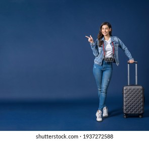 Happy young Asian woman pointing and presenting on copy space on blue color background, carry backpacker and baggage, holiday and travel concept