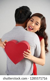 Happy young Asian woman receiving Valentines day present from her boyfriend