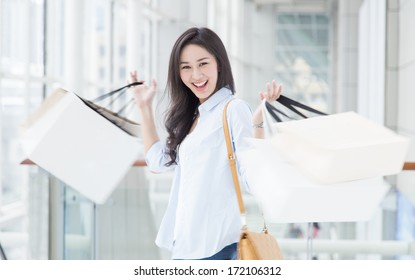Happy young Asian woman shopping with motion blur.