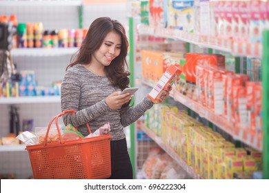 happy young asian woman shopping at supermarket with check list on her mobile phone