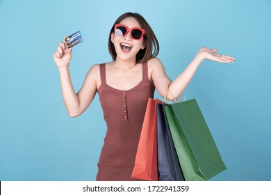 Happy young Asian woman in sunglasses holding credit card and colorful shopping bags, isolated on blue background.