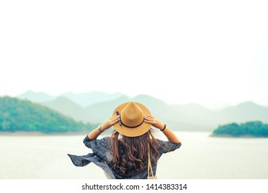 Happy young asian woman travel relax in the holiday at lake, Phetchaburi, Thailand. freedom and active lifestyle concept.