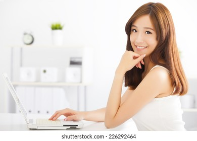 happy young asian woman using a laptop