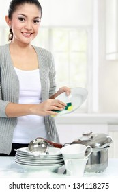 Happy Young asian Woman Washing Dishes in the kitchen