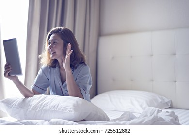 Happy young asian women greeting in a tablet video call on line sitting on bed in the bedroom at home with a blinds in the background.