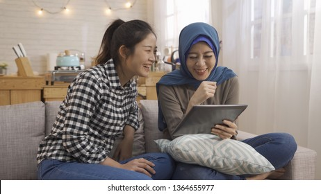 Happy young asian women using tablet PC. two multi friends watching comedy on digital pad smiling laughing cheerful while sitting on sofa at cozy home kitchen. korean and islam girls having fun.