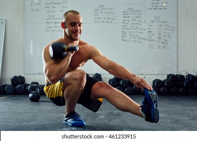 Happy young athlete doing one leg situps with kettlebell