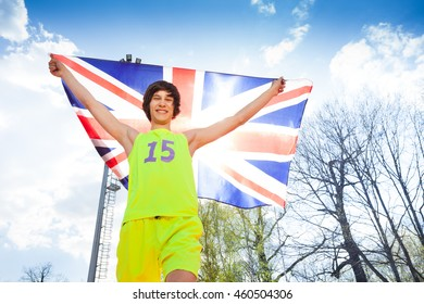 Happy young athlete running with British flag
