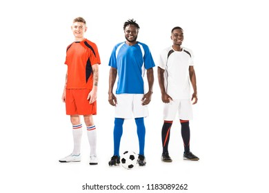 happy young athletic multiethnic soccer players standing together and smiling at camera isolated on white
