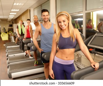 Happy young athletic people smiling in gym, standing in running machine.