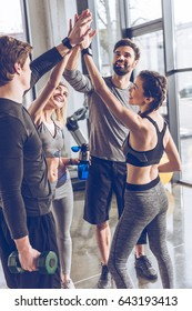 Happy young athletic people in sportswear giving high five in gym
