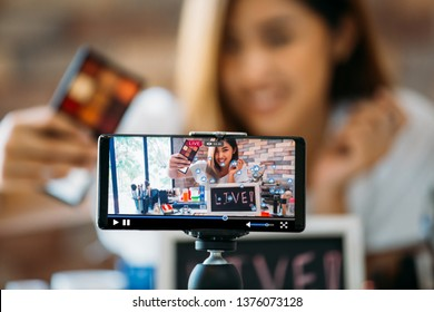 Happy young attractive Asian ethnic model filming vlog on live stream on mobile phone on tripod and showing eyeshadows at table with cosmetics