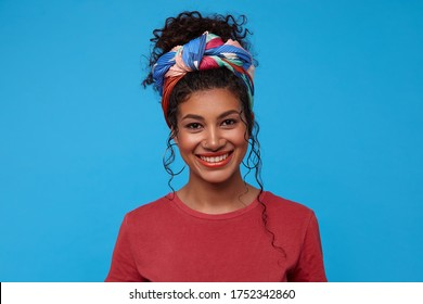 Happy young attractive dark haired curly woman with multi-colored headband showing her white perfect teeth while smiling cheerfully, isolated over blue background