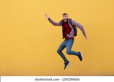 Happy young attractive ginger bearded man jumping and waving his hand, wearing in basic clothes with backpack. Looking at the camera, smiling with wide open mouth, over a yellow wall with copy space.