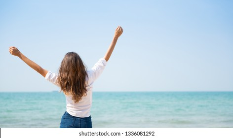 Happy young attractive woman dancing on the sea background. Successful female rising arms up in the air with Copy space. Panoramic, Banner.