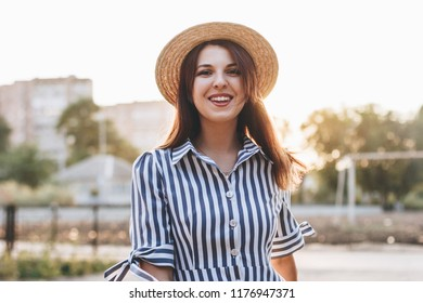 happy young attractive woman wearing striped dress and straw hat