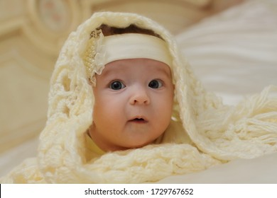 Happy young baby girl under cozy plaid. Child warms under white blanket in cold winter weather. Blanket house concept. Portrait of a cute baby in bed under a knitted blanket.