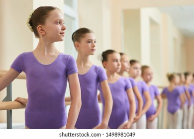 Happy young ballerina at dance lesson. Group of young ballet girls standing in row at ballet barre during ballet lesson. Professional ballet school for kids.