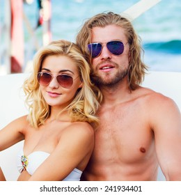 Happy young beach couple closeup portrait outdoors in sun. Young people wearing sunglasses eyewear. Athletic handsome man and young pretty woman smiling  and enjoy summer.