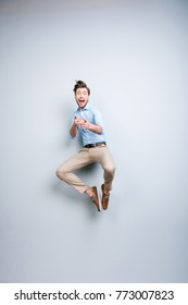 Happy, young, bearded, attractive handsome, funny man in shirt, pants  jumping in air, shouting, screaming, pointing index fingers to the camera over grey background